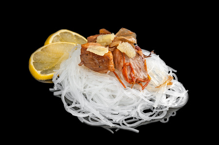 the cellophane with a piece of roasted salmon with tomatoes, onion lemon and parsley isolated on black background