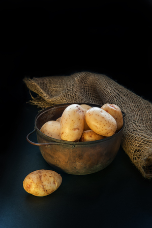 round yellow potatoes lying in the pot and on the table the lighting is low key