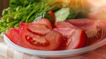 Los tomates cortaron en pedazos para la ensalada en el fondo de los pepinos y de los verdes en un día soleado.