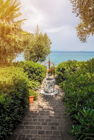 looking through an object: Beautiful Mediterranean landscape, the path leading to the sea through the garden with decoration.