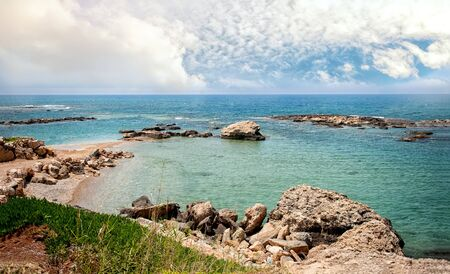 looking through an object: Beautiful views of the sea and the rocky coast of Cyprus with a cloudy sky on a Sunny day. Stock Photo