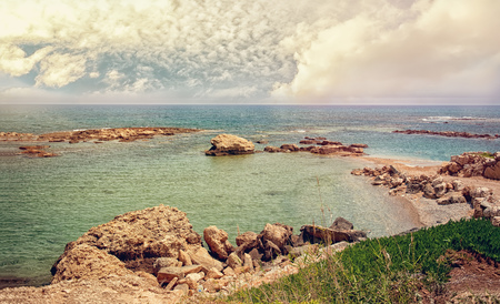 Beautiful views of the sea and the rocky coast of Cyprus with a cloudy sky on a Sunny day. The horizontal frame. Stock Photo