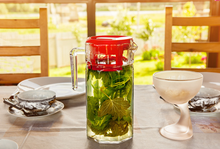 Cooling vitamin detox drink made from crushed mint leaves and currants in a large transparent glass jar with red lid is on the table. The horizontal frame.
