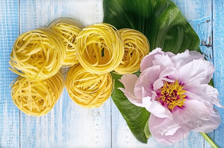 obesidad infantil: Nest pasta on a blue wooden background next to a large beautiful pink peony flower.