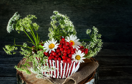 Wicker color white with red basket with a snowball, and a field of small white flowers and chamomile . Wooden background, rustic style. A horizontal frame.