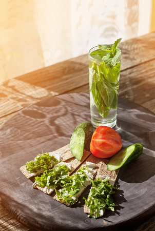 Morning easy healthy fitness Breakfast of bread with cheese and herbs and detox drink with mint and ice in the sun. Art.