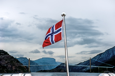 hardanger: Norwegian flag in the background of the bridge and the fjord surrounded by mountains. Cloudy weather, dramatic sky of Cumulus clouds Stock Photo