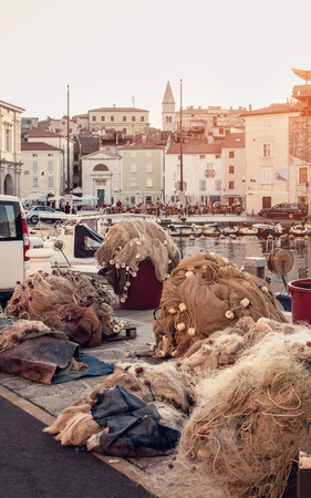trawl: Fishing nets lie on the background of the city pier. The City Of Piran , Slovenia. The horizontal frame.