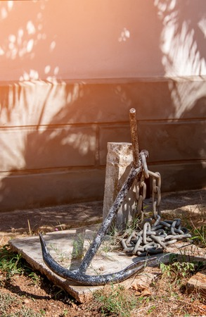 ship anchor: Old rusty anchor on land at the stone wall. The vertical frame. Stock Photo