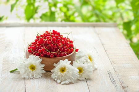 Wooden bowl with ripe red currant berries on a light background with flowers of chamomile . Copy space. The horizontal frame.