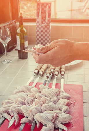 A hand puts pieces of marinated chicken on a spit in the kitchen on a Sunny day. Stock fotó