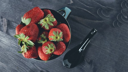 Ripe strawberries in bowl with spoon on a dark background in rustic style.