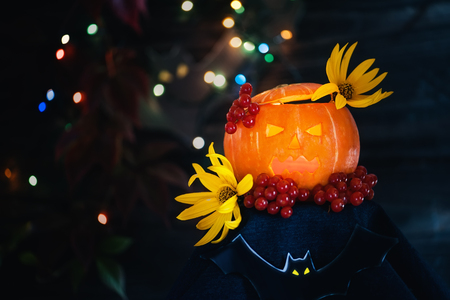 Glowing pumpkins for Halloween with yellow flowers on a dark background with . Copy the place. The horizontal frame. Stock Photo