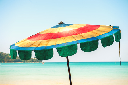 Beautiful colorful beach umbrella from striped fabric on a background of sea and sky. Stock Photo