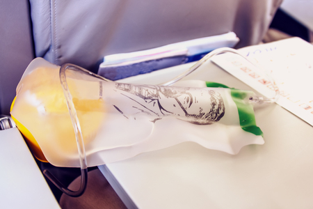 The oxygen masks for the safety of airline passengers lying on the passenger seat in the cabin.