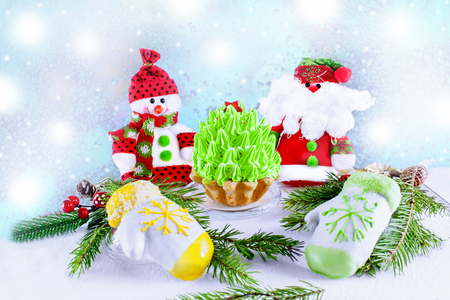 Holiday banner green Christmas tree, mittens marzipan Snowman and Santa Klais on a light wooden background. Background happy New year greeting card. Snowfall.