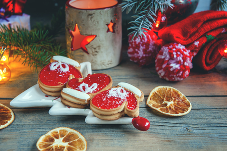 Two pie dough mittens and marmalade with black coffee on a cozy Christmas table. Close. snow. Stock Photo