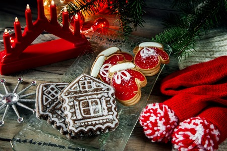 Two pie dough mittens and marmalade, with a gingerbread house on Christmas table. Copy space. The horizontal frame.