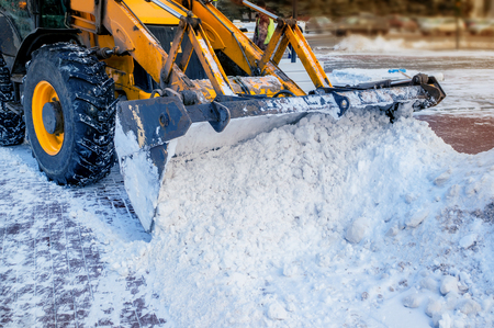Yellow bulldozer clears the street after a heavy natural snowfall. Preparing for Christmas. Sunny frosty day. Close-up. The horizontal frame.