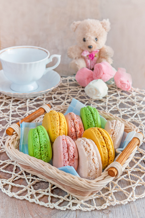 Freshly baked macarons in a wicker basket with marshmallows and a Cup of tea. The vertical frame.