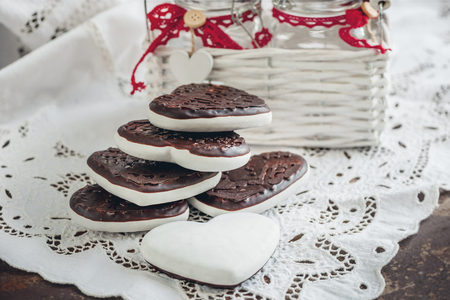 Sweet cookies in the form of hearts from gingerbread dough chocolate and a white glaze. Traditional cookies. Close up.