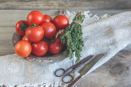 Tomatoes on a beautiful old metal plate with a thyme with a knife and scissors on a wooden table in a rustic style.