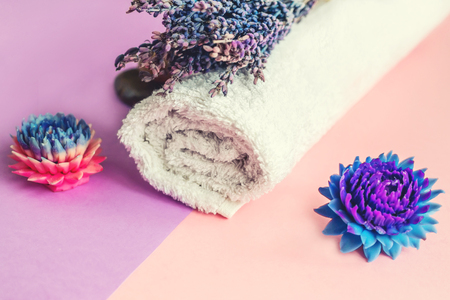 Beautiful soap in the form of flowers and towel with lavender flowers for Spa treatments on a two-tone background. Selective focus.