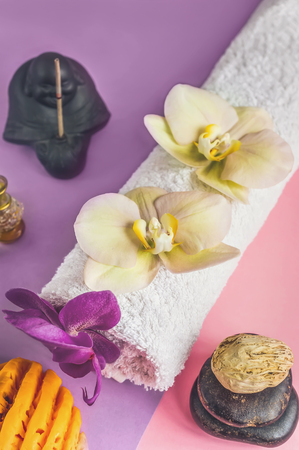 Beautiful orange handmade soap and towel with Orchid flowers for Spa treatments on two-tone background. Incense stick.
