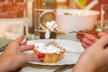 A woman holds a cupcake with white egg white cream, sitting in a cafe. Stock Photo