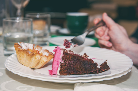 A woman eats cake while sitting in a cafe. The first steps to excess weight. High-calorie junk food. Toned.