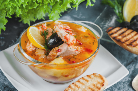 French fish soup Bouillabaisse with seafood, salmon fillet, shrimp with a rich flavor, with croutons. Delicious dinner in a transparent glass plate. Close up.