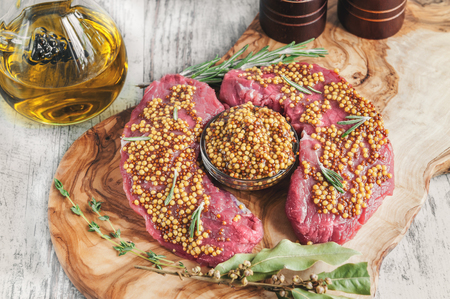 Cuts of beef for grilling on a cutting Board olive wood with pickled Dijon mustard, rosemary and herbs de Provence in a rustic style.