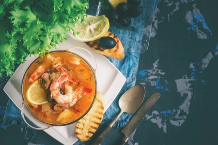 French fish soup Bouillabaisse with seafood, salmon fillet, shrimp, rich flavor, delicious dinner in a white beautiful plate. Close up. Copy spase