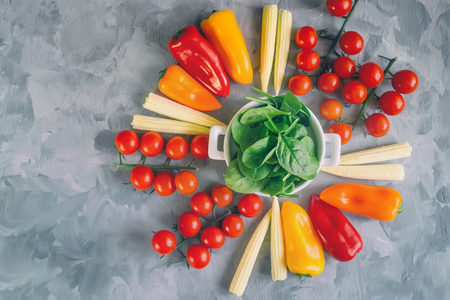 Variety of fresh organic tomato vegetables corn peppers and spinach in white Cup on beautiful background, top view, selective focus. Copy space. Imagens