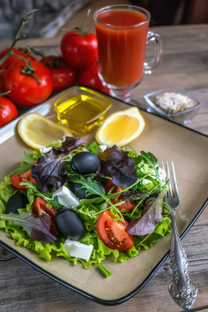 Salad diet for weight correction from the leaves of Lollo Rosso lettuce, watercress salad and other green herbs with tomatoes, olives and fitaki. Close up. The view from the top.