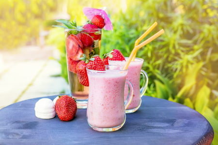 Breakfast banana smoothie strawberry detox drink of strawberries and mint with marshmallows on a green plant background. A horizontal frame.