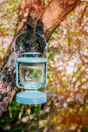 Decorative blue glass Lamp with candles hanging on a tree in the garden. Stock Photo