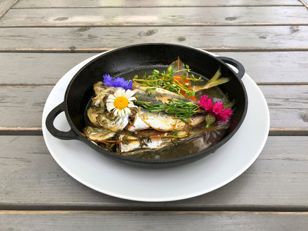 A dish of mackerel fried in a black pan for cooking and decorated with flowers. Natural food. Foto de archivo