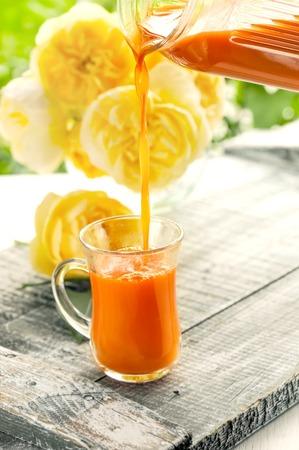 Karottensaft wird von einem Krug in eine Glasschale auf einem Hintergrund von Rosen gegossen