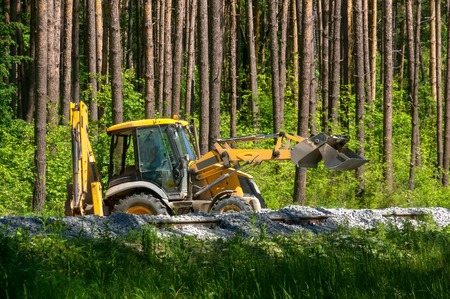 Yellow excavator pours gravel on the construction of the railway in the forest. Archivio Fotografico