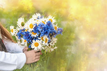 Children's hands holding a bouquet of field daisies and cornflowers on a green blurred background. Copy space. Allergy. Polinosis.