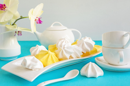 White and yellow meringue on blue background in tea serving with white kettle.