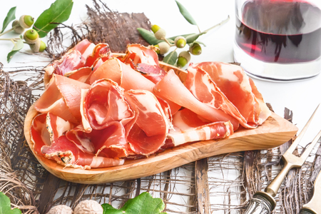 the aroma of ham and spices, thinly sliced on a white table with bread and antique Cutlery Stock Photo