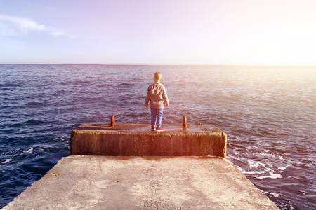 A little boy stands on the edge of a breakwater looking to the sea on a Sunny day. Danger for a child without parental care. The concept of protecting children from neglect of their parents.