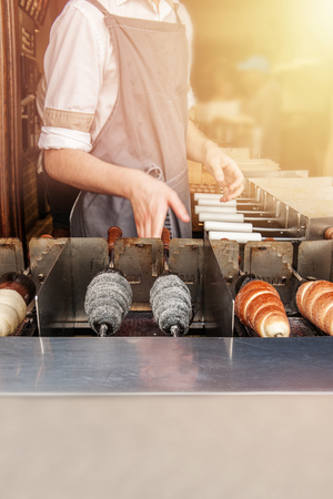 Manufacturer trdelnik in a cafe on the streets of Prague. Selective focus. Reklamní fotografie