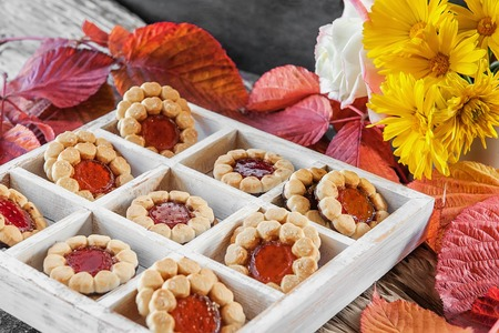 Cookies on a colored background of autumn leaves on a wooden table. Autumn mood.
