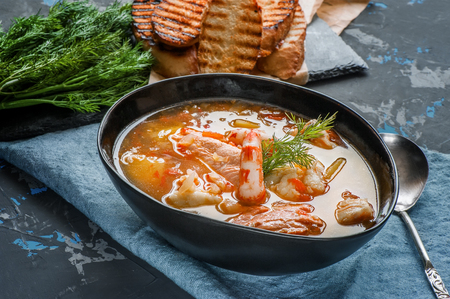 French fish soup Bouillabaisse with seafood, salmon fillet, shrimp, rich flavor, delicious dinner. Close up. Standard-Bild