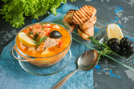 French fish soup Bouillabaisse with seafood, salmon fillet, shrimp, rich flavor, delicious dinner in a white beautiful plate.