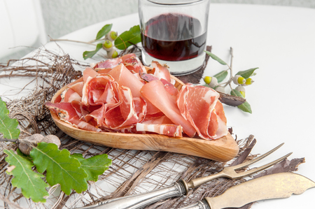 Prosciutto and jamon with spices, thinly sliced on a white table with bread and antique Cutlery.