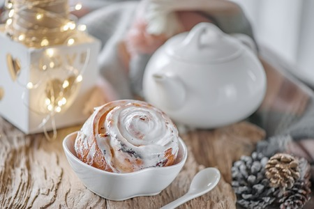 Delicious homemade sweet buns with cinnamon and icing sugar Christmas at the old wooden table. Traditional Swedish pastries, kanelbullar Reklamní fotografie - 111178897